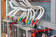 A large bundle of electrical cables or wires connected to contactors. High-power magnetic starters. Connection using a bolted connection. Large electrical Cabinet. Modern and reliable equipment.
