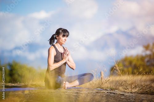 Yoga nel parco. Giovane ragazza pratica yoga all'aperto. Canvas Print