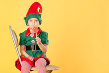 A Beautiful Baby In A Suit Of A Christmas Elf Is Sitting On A Chair. She Has A Delicious Lollipop In Her Hands. Surprise. Near Copy Space.