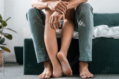 Photo cropped shot of man embracing his girlfriends legs in bedroom