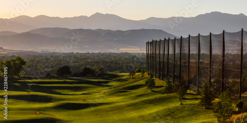 Sunlit golf course with a fence on one side Canvas-taulu