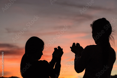 Silhouette of two women praying to god with the bible Canvas Print