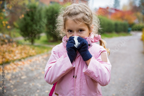 Sick little girl with cold and flu standing outdoors Tablou Canvas