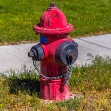 Weathered Red Fire Hydrant On A Grassy Ground