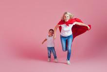Super Mom And Her Son Run Forward. Fun Family, A Young Blond Woman In A Red Cape As Superhero