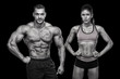 Young muscular couple posing in front of black background