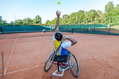 Valokuva  disabled tennis player hits the ball for service