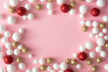 Christmas Pink Background With Copy Space Made Of Gold, Red And White Glitter Ball Decoration. New Year Greeting Card Party Minimal Style. Flat Lay