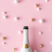 Champagne Bottle With Red, Gold And White Glitter Decoration Balls. New Year Greeting Card Party Pink Background. Minimal Style. Flat Lay Composition.
