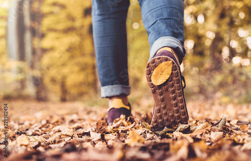 Autumn concept, close up of shoe sole with yellow leaf on it