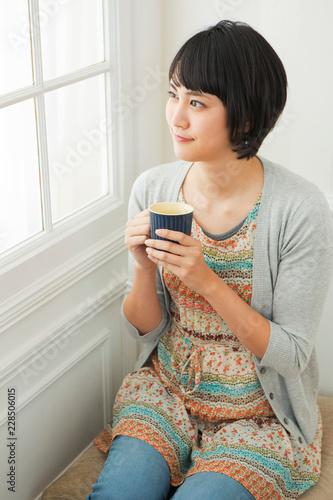 部屋でホットドリンクを飲む20代女性