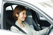 車を運転する笑顔の20代女性