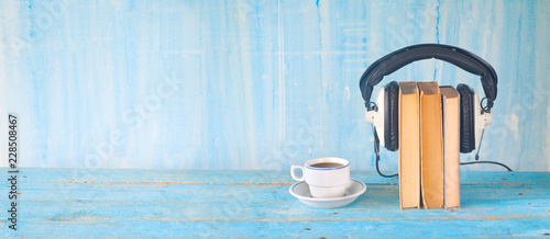 audio book concept, with books, headphones and cup of coffee, panorama, good copy space