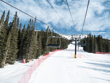 EMPTY SKI LIFTS OVER SKI TRAIL WITH PINE TREES AND BRIGHT BLUE SKY IN COLORADO, USA