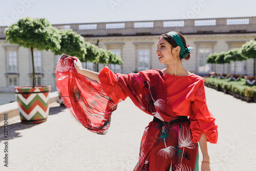 Foto  Young spanish woman in a red blouse and green pants