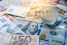Global Business And Economy. World Globe Crystal Glass On Various International Money Banknotes. Currency Exchange Rate. Financial Investment Concept