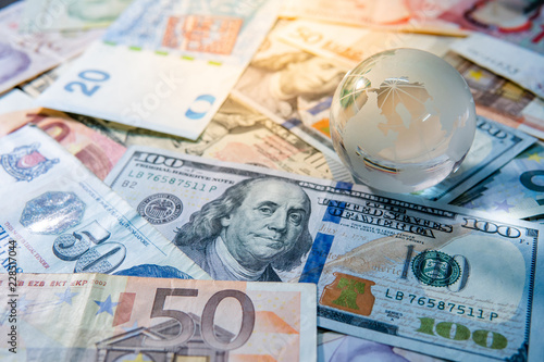 Fototapeta Global business and economy. World globe crystal glass on various international money banknotes. Currency exchange rate. Financial investment concept obraz