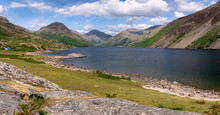 Stunning Landscape View Of Wast Water And Fells In The Lake District National Park In The UK On A Beautiful Sunny Day. Unidentified People Paddle Boarding On The Lake