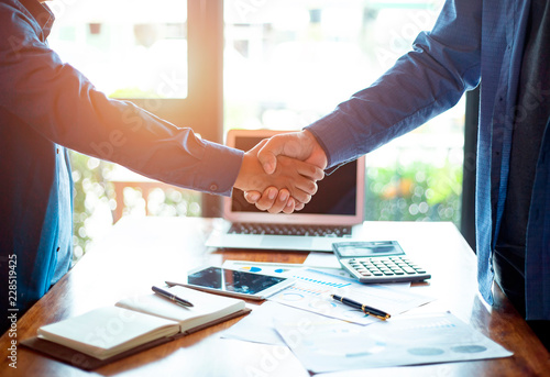 Fotomural  Successful of businessmen shaking hands after discussing good deal of trading contract in the office, Business partnership meeting and greeting concept, success, dealing, greeting and partner concept