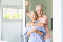 Nice Cheerful Couple Of Senior Adult People Caucasian At Home Standing Near The Window Door And Looking Outside Smiling And Having Fun Together. Happy Mature Elderly Man And Woman Retired From Work