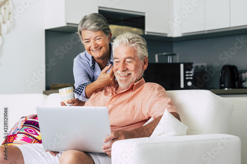 Photographie  Senior couple relaxing together in the kitchen with a laptop and with a cup of coffee or tea