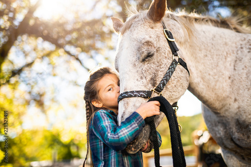 in a beautiful Autumn season of a young girl and horse Canvas Print