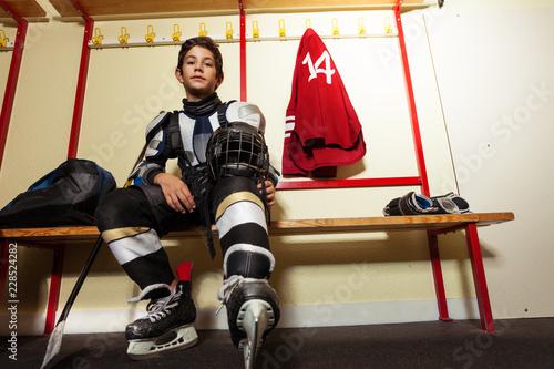 Boy getting ready for hockey game in locker room