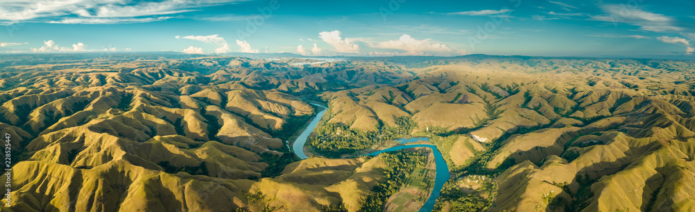 Fototapety, obrazy: Panoramic view river, hills. Aerial drone shot. Indonesia. Spectacular landscape of Sumba island. Blue sky with white clouds . Beauty of wild untouched nature.