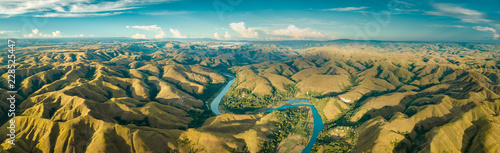 Deurstickers Luchtfoto Panoramic view river, hills. Aerial drone shot. Indonesia. Spectacular landscape of Sumba island. Blue sky with white clouds . Beauty of wild untouched nature.