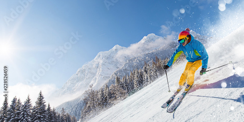 Skier skiing downhill in high mountains Wallpaper Mural