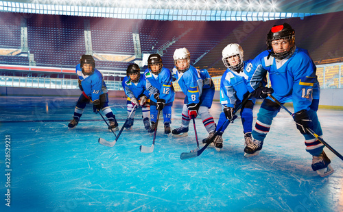 Young hockey players ready for puck on ice rink
