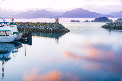 Valokuva  seascape sitka alaska, waterfront reflected sunrise colors on water