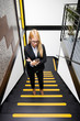 Young businesswoman using mobile phone while climbs the stairs in office