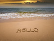 Font hand writing on sand of Hello on the beach