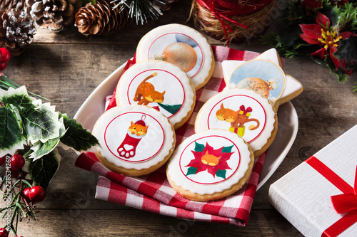 Christmas butter cookies decorated with Christmas graphics, on wooden table.