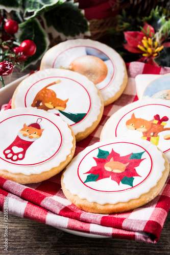 Christmas butter cookies decorated with Christmas graphics, on wooden table. Close up