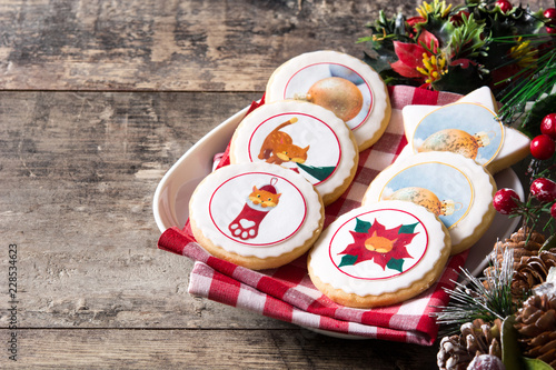 Christmas butter cookies decorated with Christmas graphics, on wooden table. Copyspace