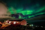 Green bright northern lights hidden by the clouds over living houses at the fjord, Nuuk city, Greenland