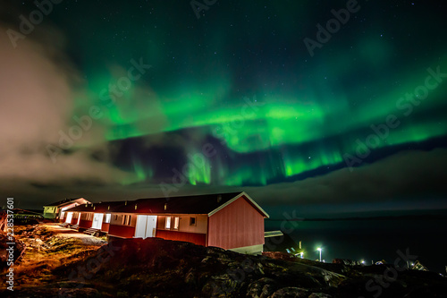 Foto auf Gartenposter Nordlicht Green bright northern lights hidden by the clouds over living houses at the fjord, Nuuk city, Greenland