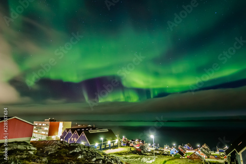 Green bright northern lights hidden by the clouds over the Inuit village at the fjord, Nuuk city, Greenland