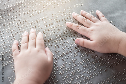Fotografie, Tablou The blind kid's hand and fingers touching the Braille letters on the metal plate