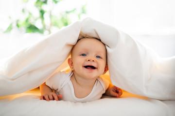 Fototapeta Cute baby girl lying on white sheet at home