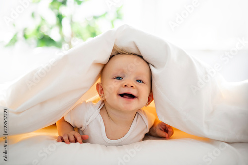 Cute baby girl lying on white sheet at home Fototapet