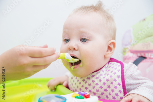 The baby learns to eat from a spoon. The first lure of the baby. Tablou Canvas
