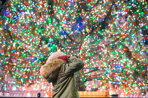 Obraz na plátně Happy girl on the background of the Rockefeller Christmas tree in New York