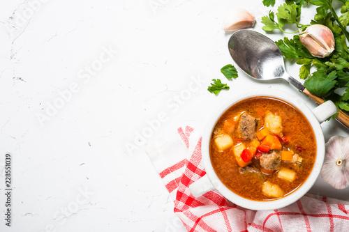 Leinwand Poster Goulash soup on white stone table top view.