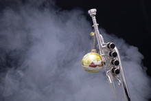A Silver Plated Piccolo Trumpet With A Christmas Ornament In Smoke On A Black Background