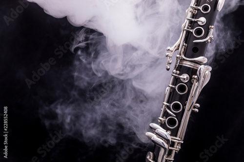 A black clarinet with silver plated keys in smoke on a black background Fototapeta