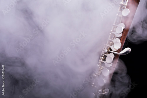 Fotografie, Obraz  A piccolo flute from brown wood with silve plated keys in smoke on a black backg
