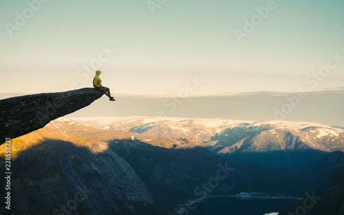 Obraz Adventurous man sitting on top of the mountain and enjoying the beautiful view during a vibrant sunset. Trolltunga rocky cliff edge in Norway mountains  - fototapety do salonu